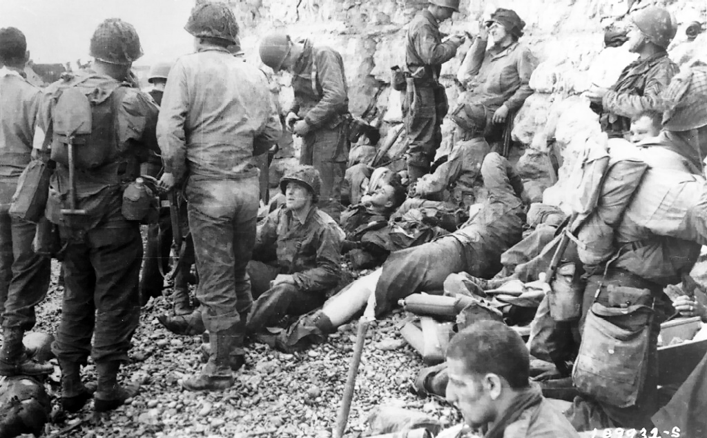 American assault troops of the 3d Battalion, 16th Infantry Regiment, 1st U.S. Infantry Division, takes a breather before moving onto the continent at Colleville-Sur-Mer