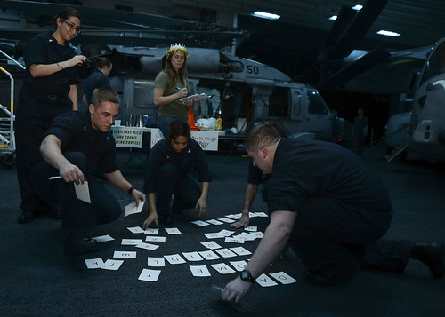 "GULF OF ADEN - Sailors aboard amphibious assault ship USS Makin Island (LHD 8) particpate in the command's Morale, Welfare and Recreation (MWR) hosted ""Reindeer Games"" ""Reindeer Scramble"" in the ship's hangar bay."