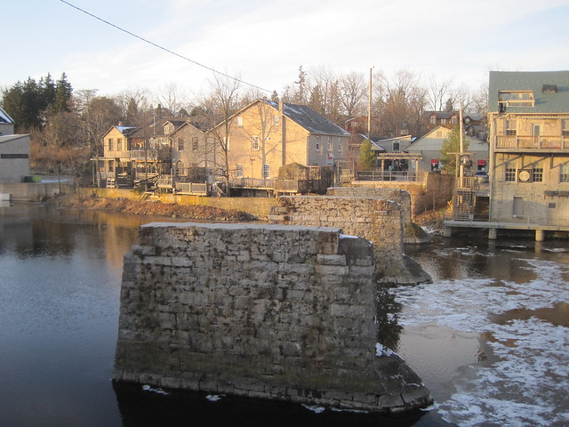 Elora's Mill Street West, viewed from across the Grand River and old walking bridge piers, in afternoon winter light, Elora Ontario Canada