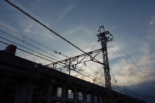 Kumagaya_1 埼玉県熊谷市の鉄道写真。 日没間際。 新幹線の高架と在来線の電線と鉄骨とラスの電柱やトラスビームのシルエットが写っている。