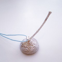 This silver acorn necklace is gold plated inside, still has its twig attached and is hung on a pretty blue silk cord.