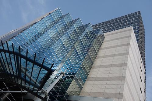 """Ikebukuro_6 池袋駅西口側で撮影した """"メトロポリタンプラザビル"""" の写真。水平方向に段々になった縦長の青いガラス張りの部分がある。 ガラス面に水平方向の枠が映り込んで幾何学模様を浮かび上がらせている。"""