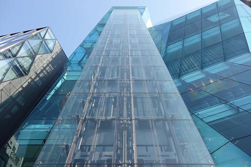 """Shibuya_26 渋谷の明治通りに面した所にある高層ビルディングを撮影した写真。 右の """"THE ICEBERG ビルディング"""" の前面はターコイズブルー色のガラス張りで複雑な三次元ジオメトリック構造をしている。 左の """"THE ICEBERG ビルディング"""" は前面が数多の三角形のガラス張りである。"""