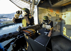 Gunner's Mate Seaman Thomas Amason mans the .50 caliber machine gun and Culinary Specialist 2nd Class Bennett Evans stands lookout aboard USS Bonhomme Richard (LHD 6) as the ship gets underway, Jan. 10. (U.S. Navy/MC3 Christian M. Caldwell)