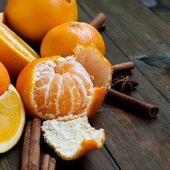 tangerines, oranges and cinnamon sticks on a woode…