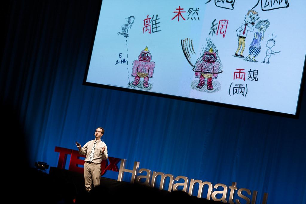 写真:魑魅魍魎の漢字を覚えるためのイラストが投影されたスクリーンの前でスピーチするブレットさん