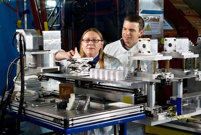 Amy Clarke and Seth Imhoff of Materials Technology-Metallurgy (MST-6) align a copper density calibration object for a proton radiography experiment.