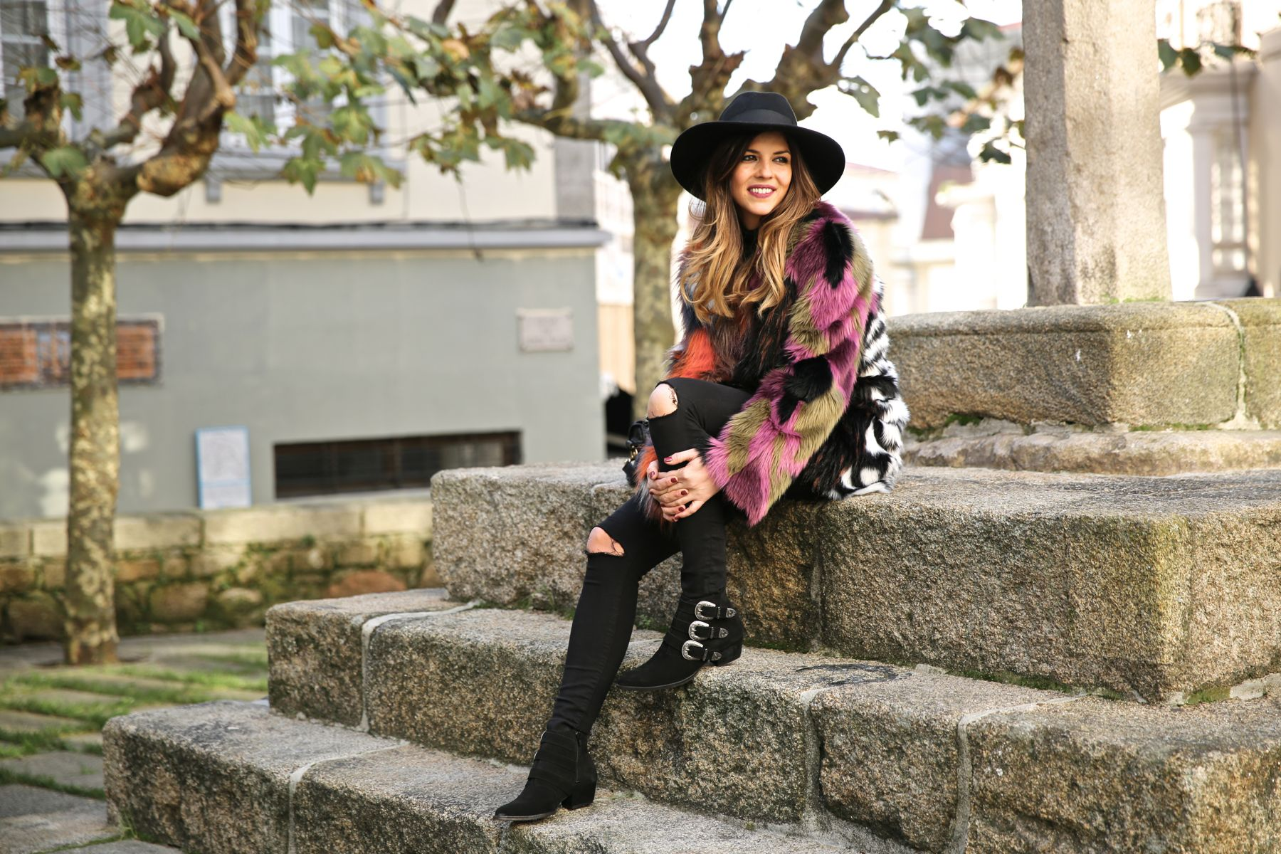 Look boho chic con vaqueros pitillo negro, sombrero fedora, abrigo de pelo y botines camperos