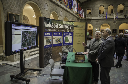 Jim Fortner, of the Natural Resources Conservation Service (NRCS) Natural Resources Soil Science, in Lincoln, NE (left) explains the Web Soil Survey to Richard Derksen, of the USDA Office of the Chief Scientist,  at the celebration of the International Year of Soils at USDA in Washington, D.C. on Tuesday, Jan. 6, 2015. The Web Soil Survey is a description of soil survey maps across the country. The event was to highlight the importance of healthy soils for food security, ecosystem functions and strong farms and ranches. USDA photo by Bob Nichols.