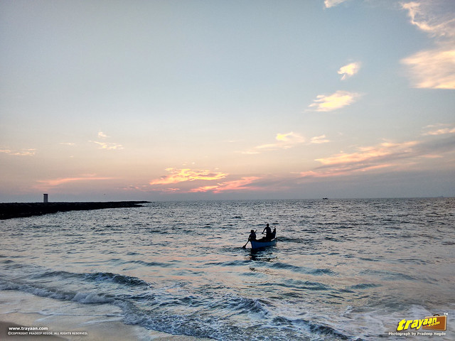 Fishermen on their boat, returning at sunset on an evening in Panambur Beach, Mangalore, Mangaluru, Dakshina Kannada, Karnataka, India