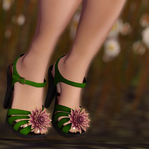 Image Description: Closeup of feet wearing green sandals with spiky pink flowers on the toes.