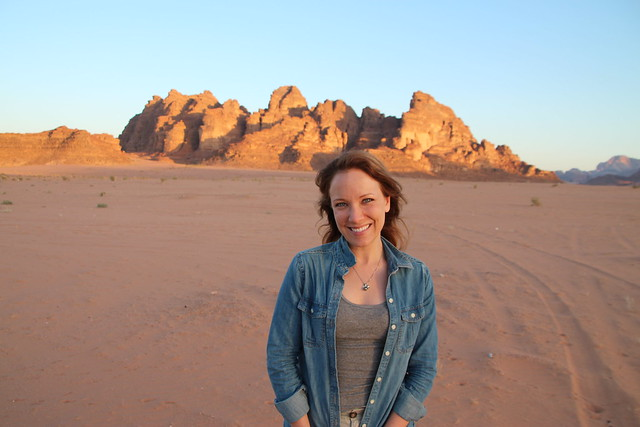 Rachelle In the dessert in Jordan wearing a long sleeve shirt over a tanktop.