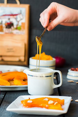 pour a teaspoon honey in ceramic ware, baked pumpk…