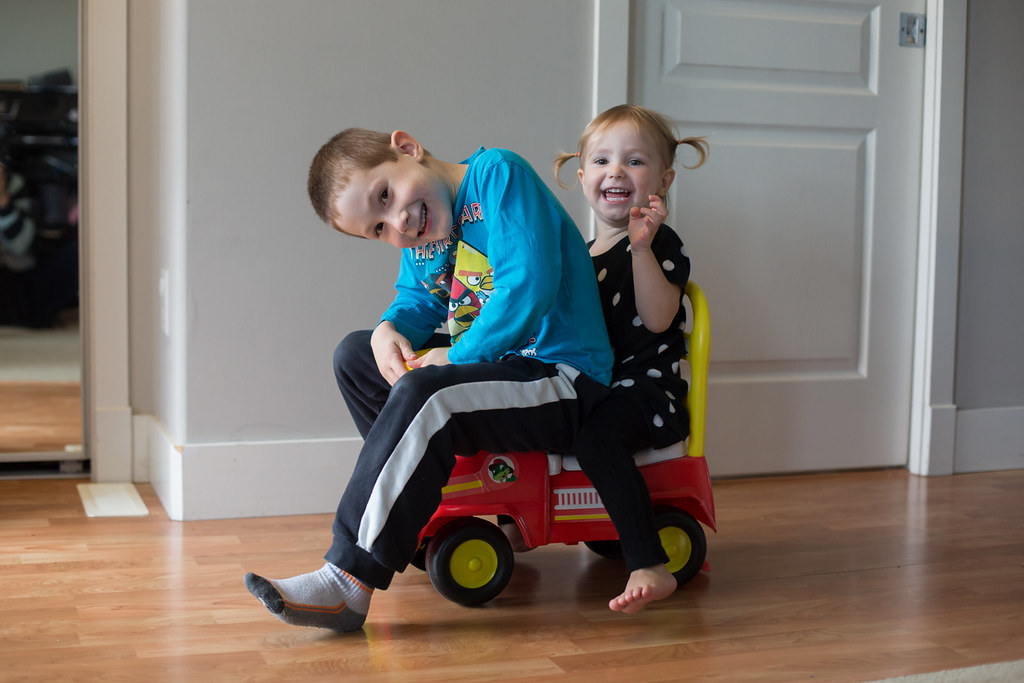Siblings on a toy car