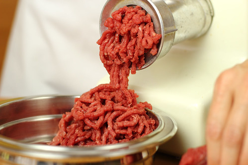 Raw beef being ground into a bowl.