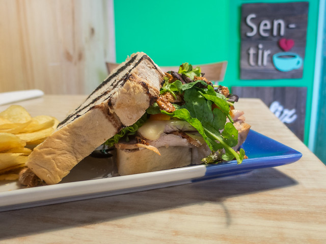 Turkey sandwich with cherry tomatoes, emmental cheese, lettuce, candied peanuts and balsamic vinegar on artisanal bread