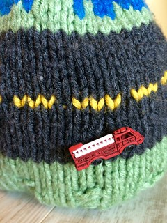 Nothing ever happens on my block hand knit child's hat with fire truck and police car buttons