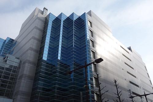 """Ikebukuro_2 池袋駅西口側で撮影した """"メトロポリタンプラザビル"""" の写真。 水平方向に段々になった縦長の青いガラス張りの部分がある。"""