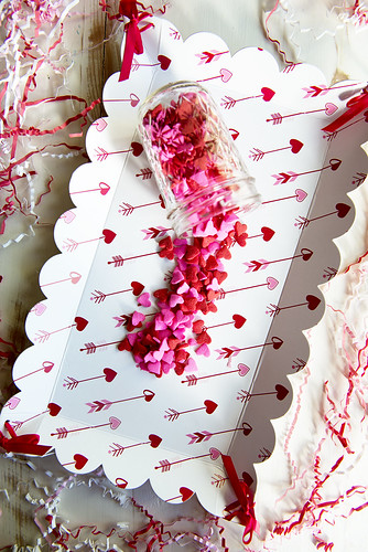 heart shaped candy sprinkles on a table and a glass mason jar on a decorative Valentine's Day tray