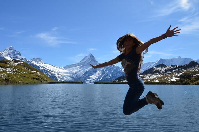 Saltando frente al maravilloso lago Bachalpsee con los brazos abiertos