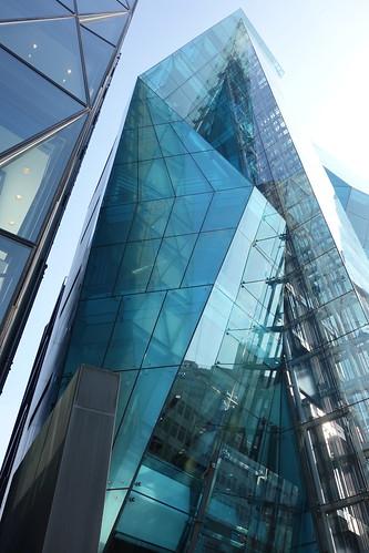 """Shibuya_22 渋谷の明治通りに面した所にある高層ビルディングを撮影した写真。 """"THE ICEBERG ビルディング""""。 建物の前面はターコイズブルー色のガラス張りで複雑な三次元ジオメトリック構造をしている。"""
