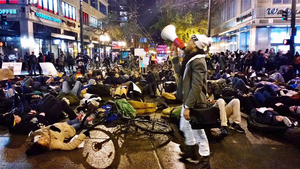 a protest in seattle, where many people are lying down in the middle of the street and one person talks on a bullhorn