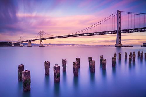 sanfrancisco california longexposure sunset clouds reflections dusk baybridge pillars