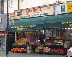 "A terraced shopfront with a display of vegetables outside on the pavement.  A sign above reads ""Savemore World of Frozen Foods"".  A dark green canopy hangs above the vegetables, and a customer can just be seen inside, leaning over a glass counter."