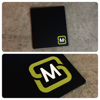 Custom graphic design portfolio book in matte black acrylic with engraved color fill treatment