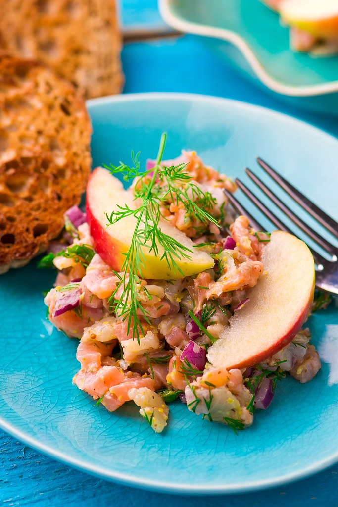 fish tartare  with apple on a blue plate.