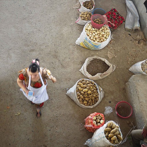 woman potatoes onions bazaar uzbekistan centralasia samarkand moblephone chorsumarket bigsacks