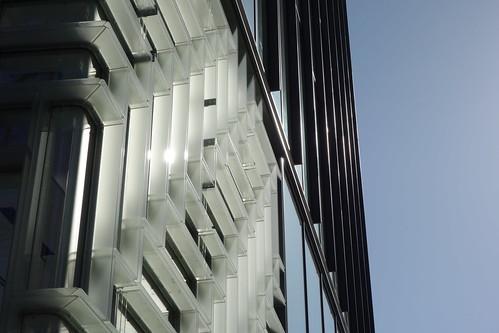 """Shibuya_8 表参道のビルディングを撮影した写真。 """"oak omotesando"""" である。 建物の一部を撮影したもの。 飛び出たガラス板で幾何学模様の装飾が作られている。"""