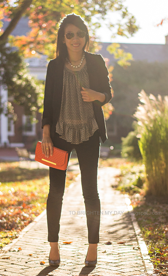 black boyfriend blazer, patterned ruffled top, orange clutch, black pants