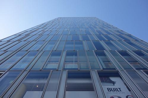 "Aoyama_3 青山通りの ""Ao"" のビルディングを撮影した写真。 全面ガラス張り。 直下から見上げて撮影したもの。"