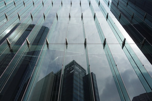 """Shimbashi_11 新橋で撮影した高層ビルディングの写真。 """"汐留住友ビル""""。 下層部分の緑色掛かったガラス張りの壁面を正面から撮影したもの。 ガラス張りの下層部分の上から下まで連なった垂直なガラス板が左端から右端まで等間隔に突き出ている。 向かい側の高層ビルディング群が映り込んでいる。"""