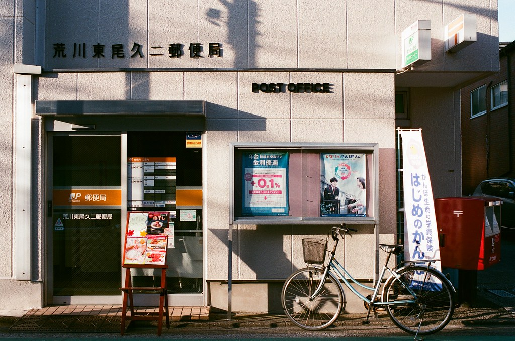 荒川東尾久二郵便局 Tokyo, Japan / AGFA VISTAPlus / Nikon FM2 荒川東尾久二郵便局,那時候剛到荒川,記得買了兩只 EMS 郵便帶,想說從京都一路上蒐集的文宣品可以慢慢的裝滿然後寄出。  後來的確是寄出了,而且也有相當驚人的重量,真的就是蒐集很多。  我習慣會拿兩份,一份寄回高雄的家、一份就寄出去。  但後來結果如何,我就一直沒詢問了,不過好像也不是那麼重要的事。  Nikon FM2 Nikon AI AF Nikkor 35mm F/2D AGFA VISTAPlus ISO400 0994-0019 2015/09/30 Photo by Toomore