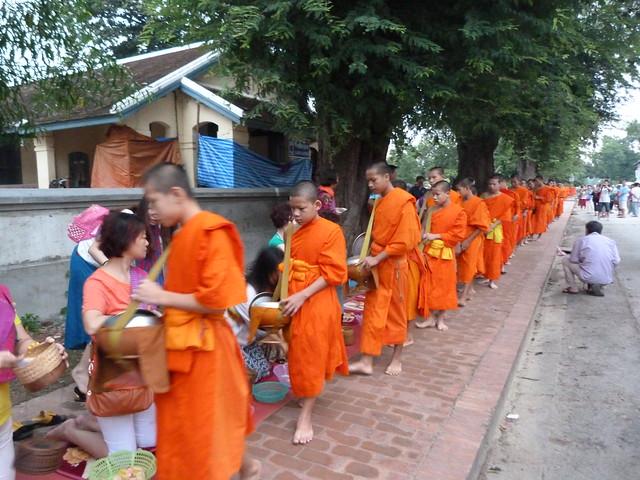 Desfile de monjes budistas en la calle principal de Luang Prabang durante el tak bat