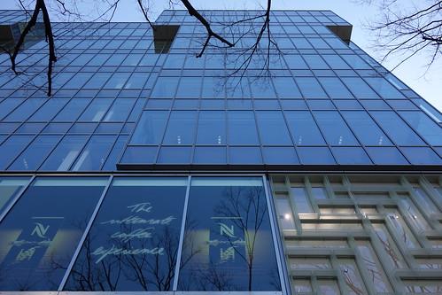 """Shibuya_7 表参道のビルディングを撮影した写真。 """"oak omotesando"""" である。 直下から見上げる角度で撮影したもの。 全面ガラス張りで隣の建物が映り込んでいる。 落葉した並木の枝が写真に写っている。"""