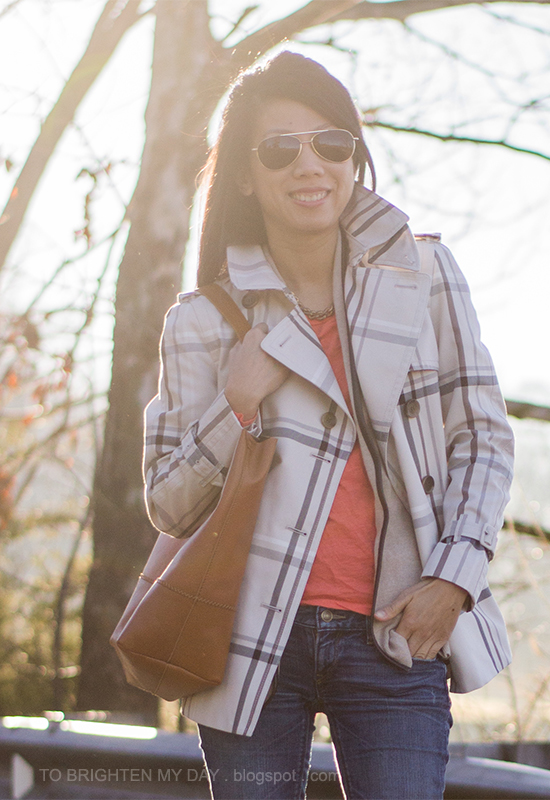 plaid patterned trench jacket, camel sweater, orange tee, cognac brown tote