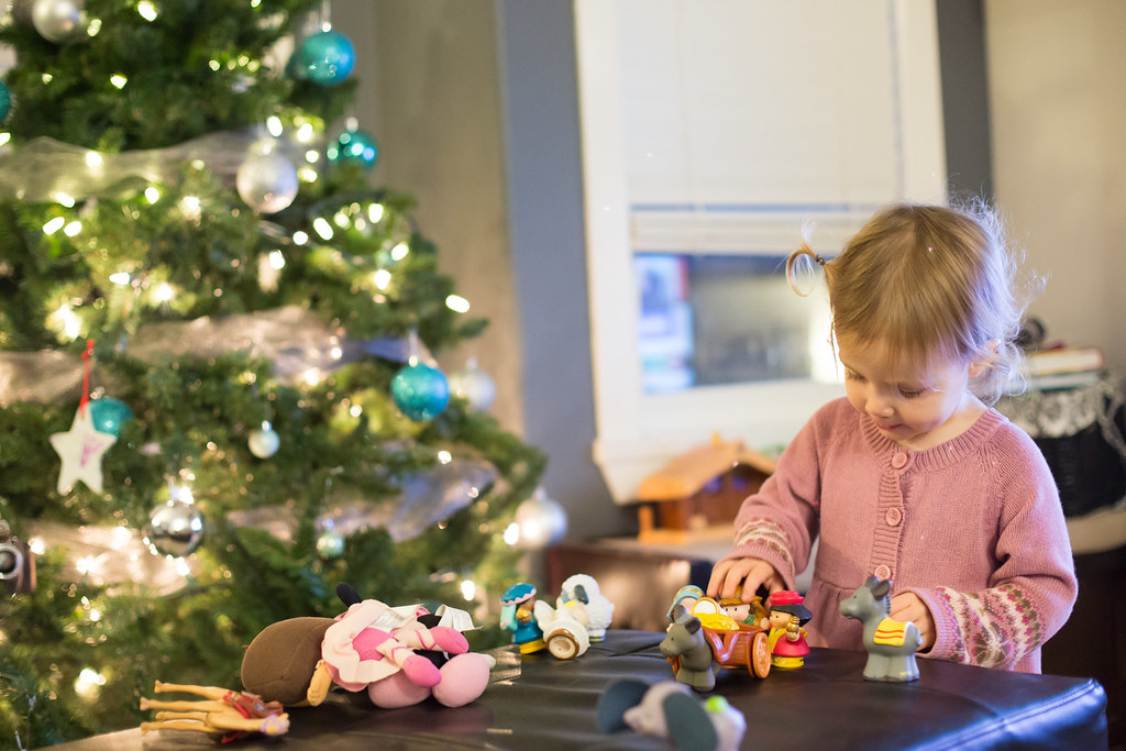 Girl playing with nativity scene in front of Christmas tree