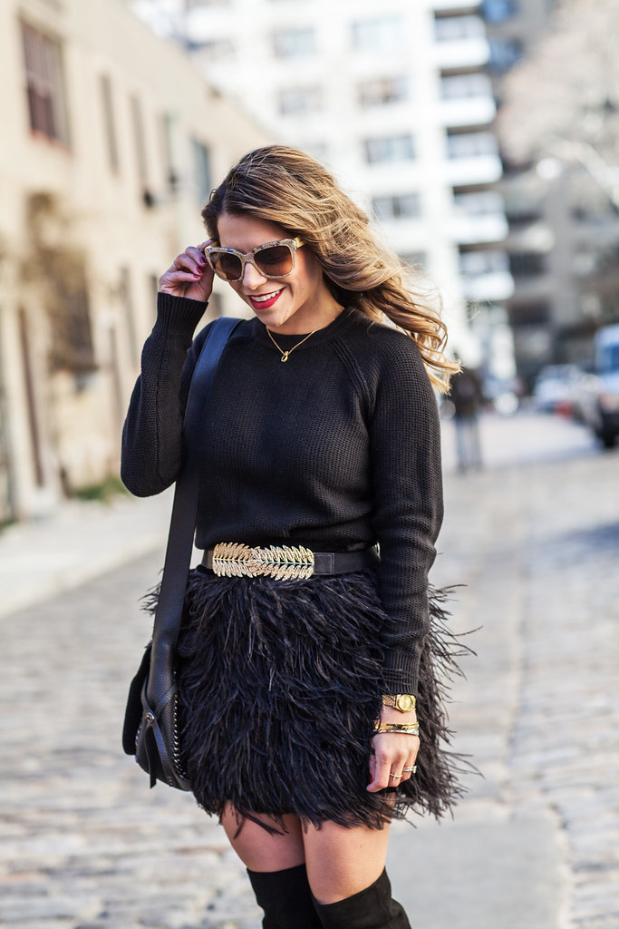 sam edelman feather black skirt joie olivia boots over the knee side black boots coach dakotan flap crosbody dolce and gabbana gold sunglasses layering banana republic black knew sweater bdbg gold belt how to wear a belt with a feather skirt nyc fashion blogger all black outfit winter outfit ideas holiday outfit ideas what to wear when going out in the winter corporate catwalk