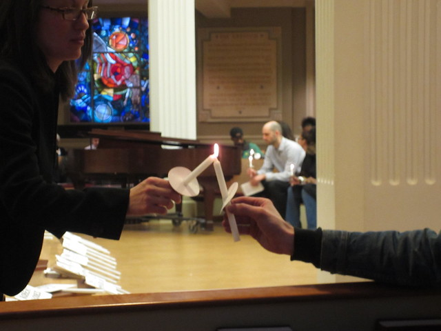 A Homeless Persons' Memorial Day vigil attendee helps light the memorial candle of another.    Photo by Eric Falquero