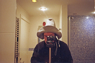 reflected self-portrait with Yashica T4 camera and pointed felt hat