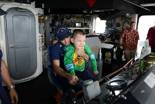 Six-year-old Jacob Butierries sits at the helm of the Coast Guard Cutter Rush with the support of his father Petty Officer 1st Class Denis Butierries during a tour of the ship in Honolulu Dec. 23, 2014. Jacob was diagnosed with spinal muscular atrophy when he was four months old and was given between four months an one year to live. His longtime wish was to see the Rush where his grandfather served as the engineering officer.  (U.S. Coast Guard photo by Chief Petty Officer Kurt Fredrickson)