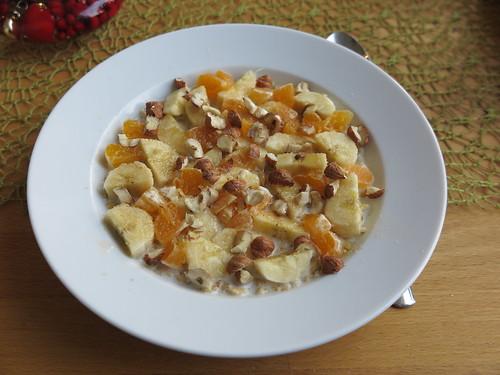 Frisch geflockter Nackthafer mit Banane, Mandarine, Haselnüssen, braunem Zucker und Milch