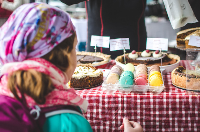 A young girl ponders dessert options at a pastry stall in the Prague Farmer's Market.