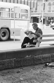 Street scene, man in foreground reading a newspaper while sitting on a bench seat
