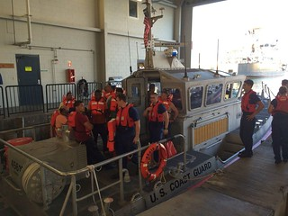 Coast Guard crew members stand with 11 survivors of the Tug Nalani at Coast Guard Station Honolulu, Jan. 22, 2015. The tug sank approximately two and a half miles off of Barbers Point Harbor, Oahu and all 11 people were rescued. (U.S. Coast Guard photo by Lt. Kevin Cooper)