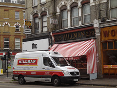 "A terraced shopfront near a street corner, with ""HILLMAN"" signage above and the red-and-white striped canopy typical of a butchers shop.  A Hillman-branded white van is parked outside."