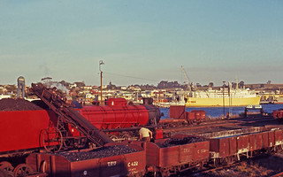 Photographed on 26 March 1970 of Tasmanian Railways H class No H 2 being re-coaled with the Princess of Tasmania moored at a wharf across the Mersey River at Devonport, Tasmania, Australia.